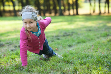 Preschool girl making push-ups exercices with one hand on grass