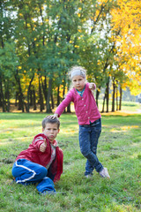 Boy showing thumb up and girl thump down in autumn park