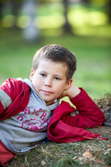 Pensive boy in red jacket laying on grass, looking at camera