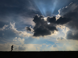 Lonesome jogger Dramatic sky with jogger running - backlighting