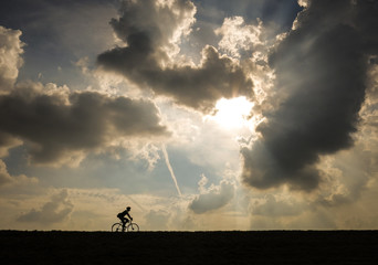 byciclist - a man riding his bike in front of a dramatic sky
