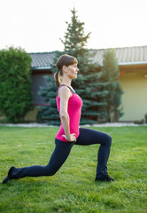Sporty woman doing lunge exercise in sunset