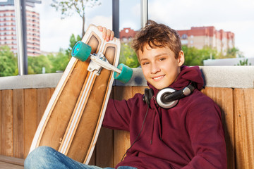 Positive cute boy holds skateboard while sitting