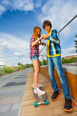 Smiling boy and girl on skateboard hold hands