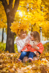 mother and her baby have fun in the autumn park