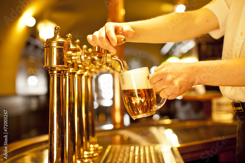 gold beer in the hand and beer taps - 72003267