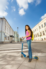 Small smiling girl stands on scooter in the city