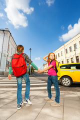 Boy with girl hold hands and stand near road