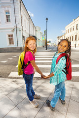 Two happy girls hold hands, stand near crossroad