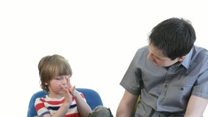 teenager boy talking to preschooler brother