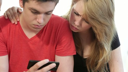 Couple of teenagers looking at a smart phone