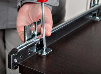 Assembling of furniture, install  drawer slides, screwing screw