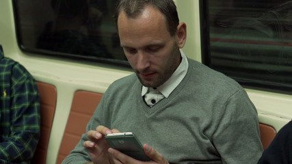 Man traveling by metro and using smartphone, steadycam shot