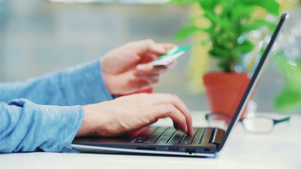 Young man shopping online with credit card