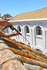 Worker cleaning a roof with high pressure water