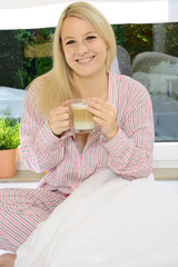 Frau in Pyjama trinkt Kaffee im Bett