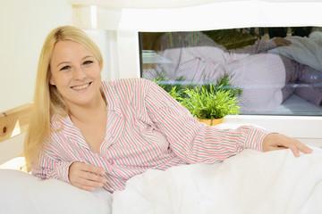 Frau in Schlafanzug liegt entspannt im Bett
