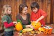 Woman helping kids to carve jack-o-lanterns