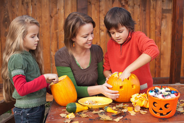 Woman helping kids to carve jack-o-lanterns