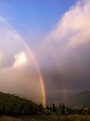 Regenbogen vor bergiger Kulisse