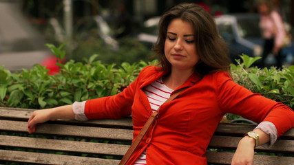 Woman sitting on the street bench and relaxing, steadycam shot