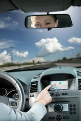 Woman using gps navigator in a car