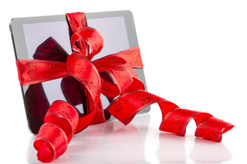 Tablet pc with Christmas red ribbon on white
