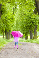 little girl wearing rubber boots with umbrella in spring alley