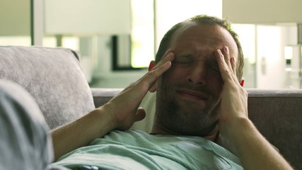 Man having headache and lying at home on the sofa