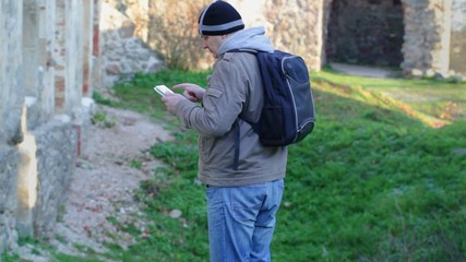 Hiker with tablet PC and backpack in ruins