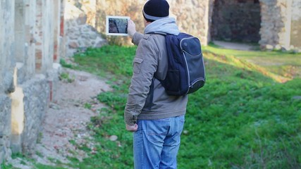 Hiker filmed with tablet PC in ruins