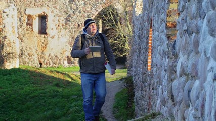 Hiker filmed with tablet PC ancient wall
