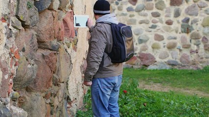 Hiker with tablet PC near ancient wall