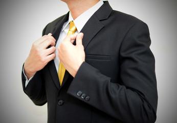 Asian handsom businessman wearing black suit correcting his suit