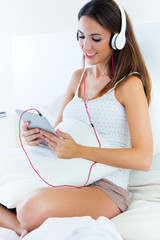 Beautiful young woman listening to music with tablet sitting on