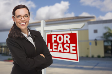 Woman In Front of Commercial Building and For Lease Sign