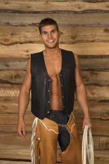 cowboy wood behind black vest hold rope look
