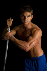 man fitness no shirt on black hold pole looking