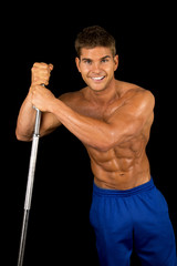 man fitness no shirt on black lean on pole smiling