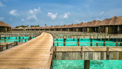 wooden path to the bungalows on irufushi island, maldives