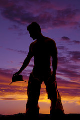 silhouette cowboy no shirt hold hat down look side