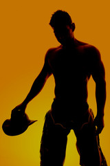silhouette cowboy no shirt hold hat down
