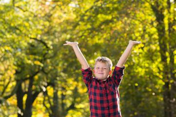 Knabe im Park streckt Arme in die Luft