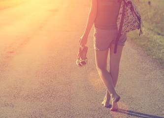 Sexy traveler barefoot woman walking on highway