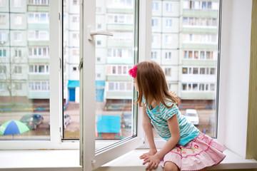 Девочка смотрит в открытое окно