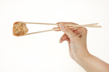 Hand holding chinese Wonton dumpling with chopsticks