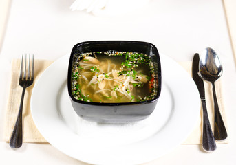 Bowl of chicken noodle soup with fresh herbs