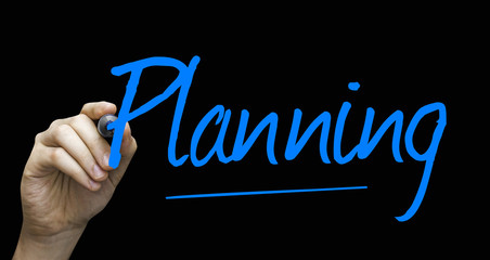 Planning hand writing with a blue mark on a transparent board