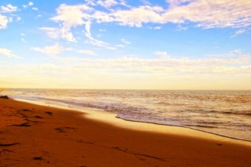 Beach with cloudy blue sky and beautiful sand