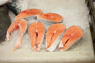 fresh salmon steaks on wooden pad